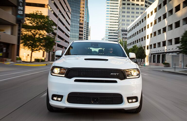 2019 Dodge Durango SRT exterior front shot with white paint color driving through a city during the day