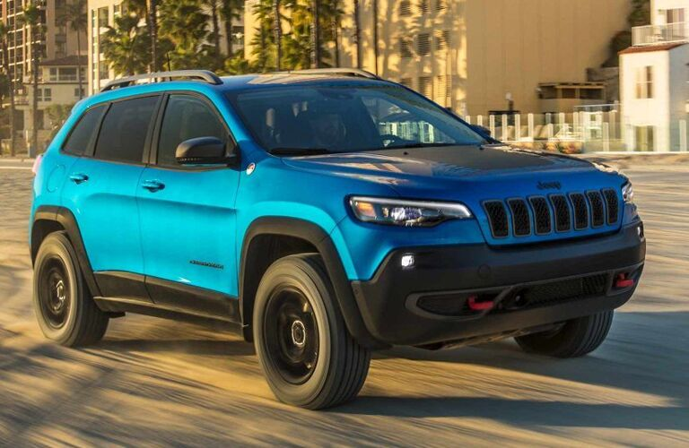 2019 Jeep Cherokee exterior shot with blue teal paint color driving on a beach near palm trees and beachfront property