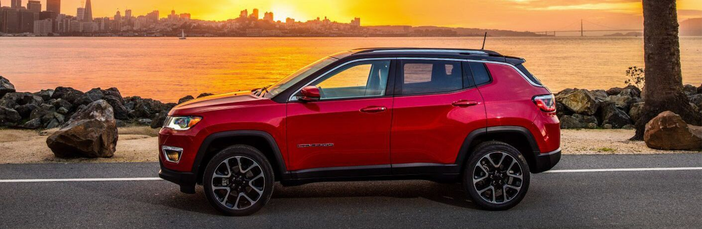 2019 Jeep Compass exterior side shot with red paint color parked by a beach as the sun sets over a city skyline