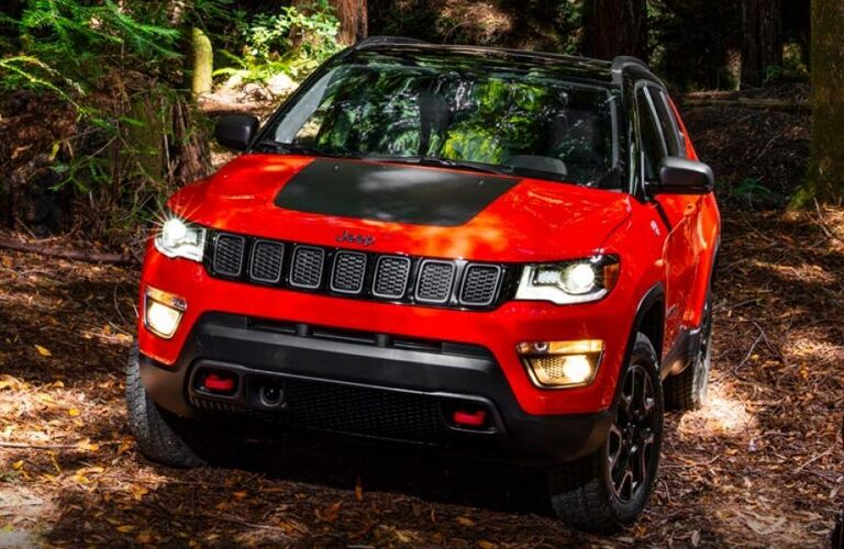 2019 Jeep Compass exterior front shot with red and black paint color driving through a dirt off-road forest path