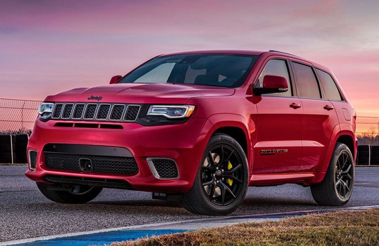 2019 Jeep Grand Cherokee exterior shot with red paint color parked on the edge of a race track