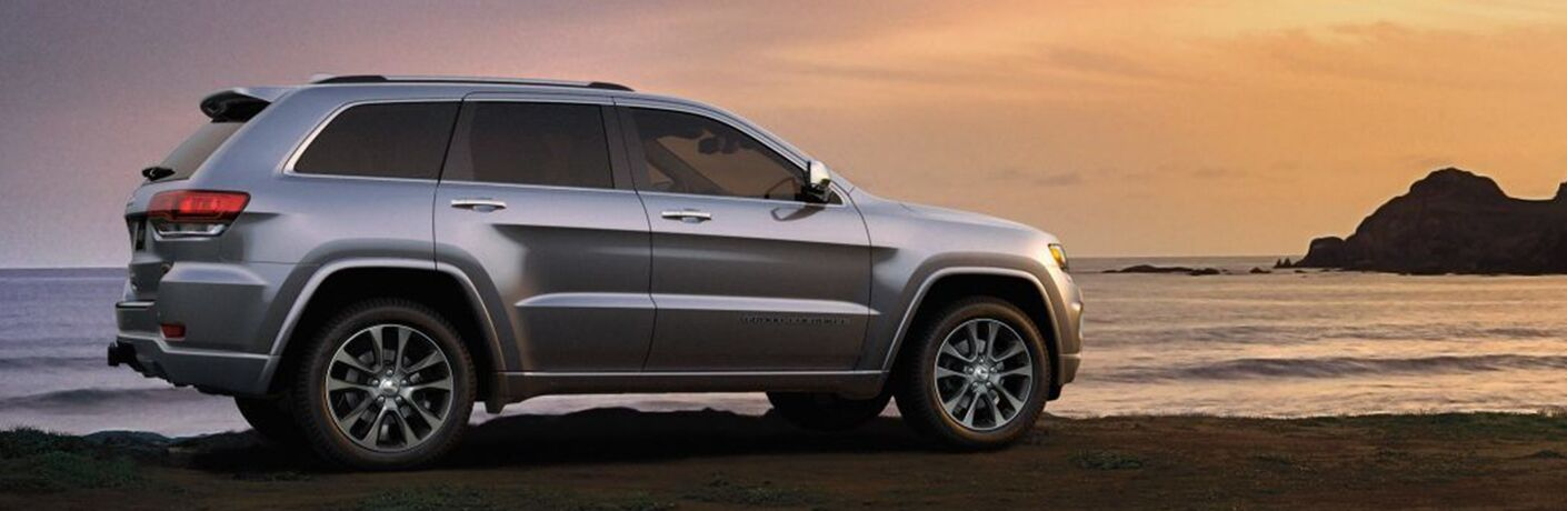 Profile view of silver Jeep Grand Cherokee overlooking body of water