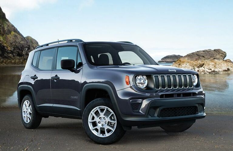 2019 Jeep Renegade exterior shot parked on a beach near water and giant rocky cliffs and formations