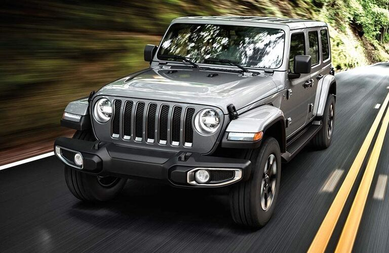2019 Jeep Wrangler exterior front shot with gray metallic paint color driving alongside a grassy cliff on a highway