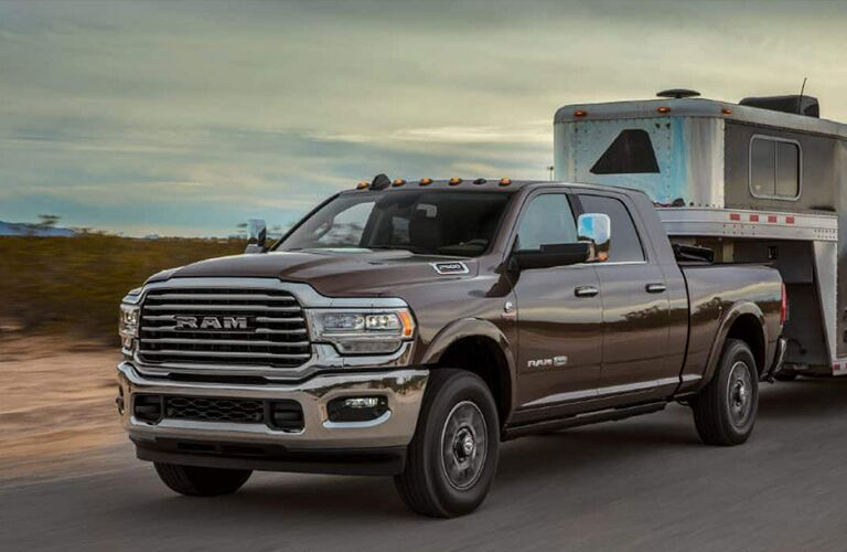 2019 Ram 2500 exterior shot towing a small trailer down a country road