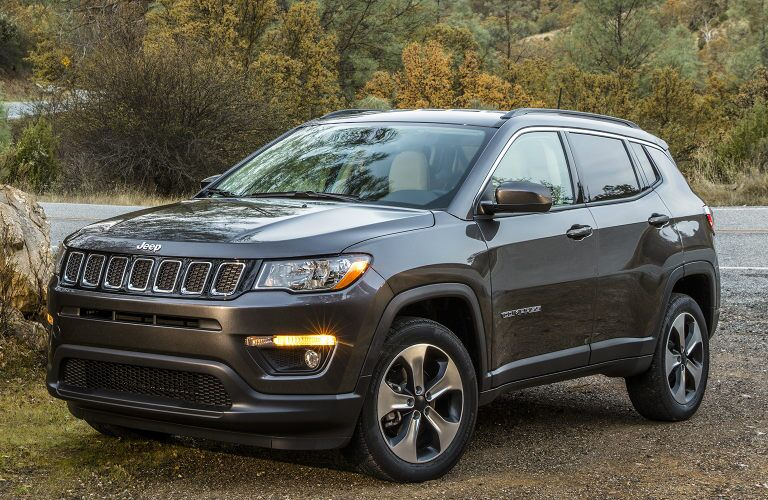2019 Jeep Compass exterior shot with gray metallic paint color parked on a rocky beach near a river