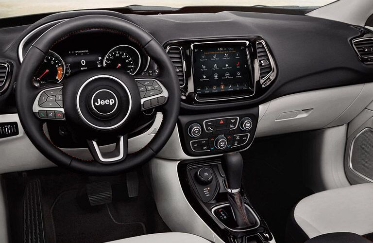 2019 Jeep Compass interior shot of steering wheel, transmission, and dashboard layout with infotainment screen