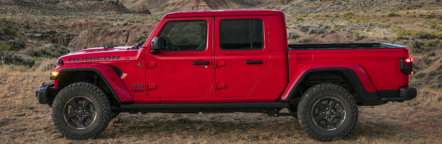 2020 Jeep Gladiator Rubicon exterior side shot with red paint color parked in a wilderness of wild dry grass and hills