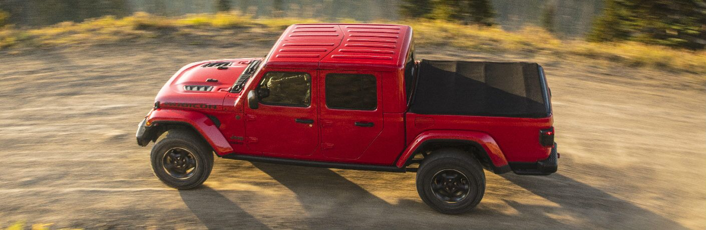 2020 Jeep Gladiator exterior overhead shot with red paint color driving on a dirt road
