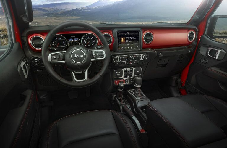 2020 Jeep Gladiator interior shot of front seating, dashboard design, and steering wheel with Jeep logo badge