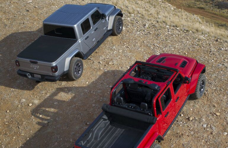 exterior overhead shot of 2 2020 Jeep Gladiator models in red and gray paint color parked on a gravel plain