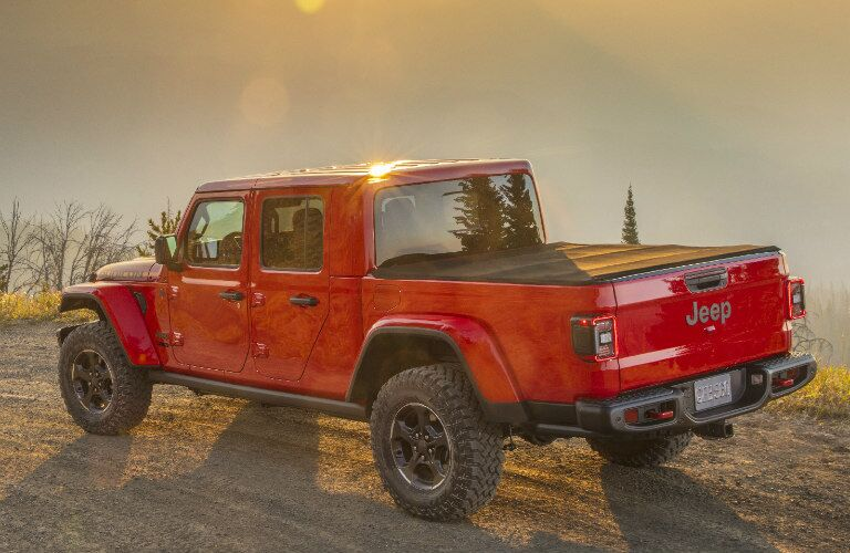 2020 Jeep Gladiator exterior side shot with firecracker red paint color parked on a gravel dirt road as the sun shines in the background