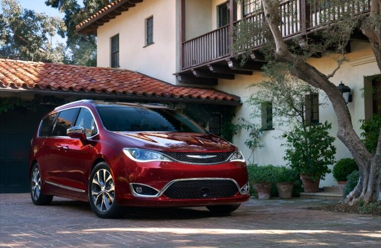Red 2020 Chrysler Pacifica parked in front of modern-styled house