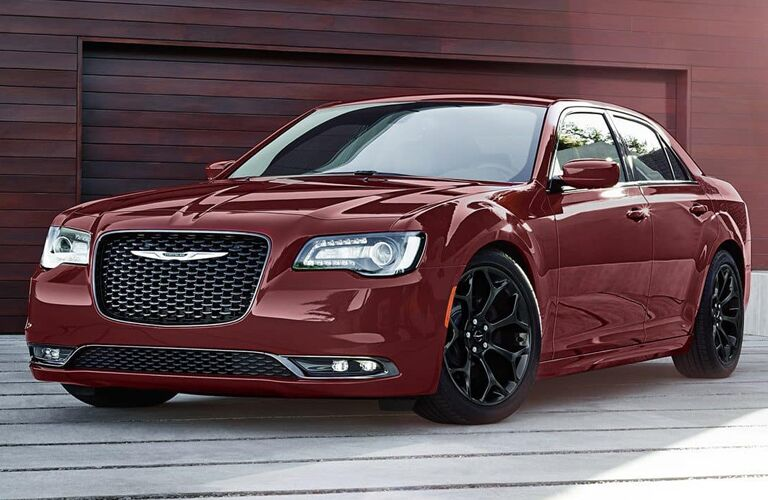 2019 Chrysler 300 exterior shot with dark red paint color parked on a wooden pier with a red wood cabin garage behind it