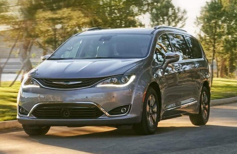 2019 Chrysler Pacific minivan exterior shot with silver metallic paint color driving through a forest park in the summer