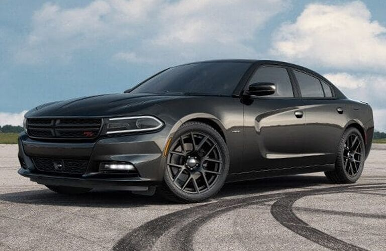 2019 Dodge Charger exterior side shot with dark gray paint color parked on an empty lot near tread drifting marks with clouds in a blue sky behind it