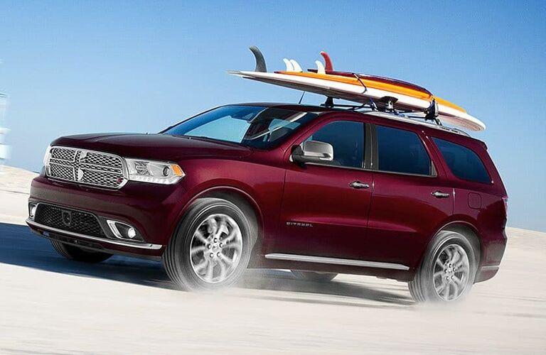 2019 Dodge Durango exterior side shot with red purple paint color driving on a sand dune and kicking up dust with surf boards on its roof rack rails
