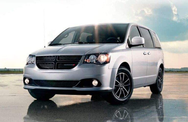 2019 Dodge Grand Caravan exterior shot with silver paint color parked on the wet sand of a beach under a bright sun