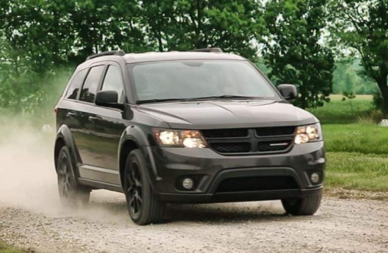 2019 Dodge Journey exterior shot with black paint color driving on a gravel road in a forest as dust kicks up from the wheels