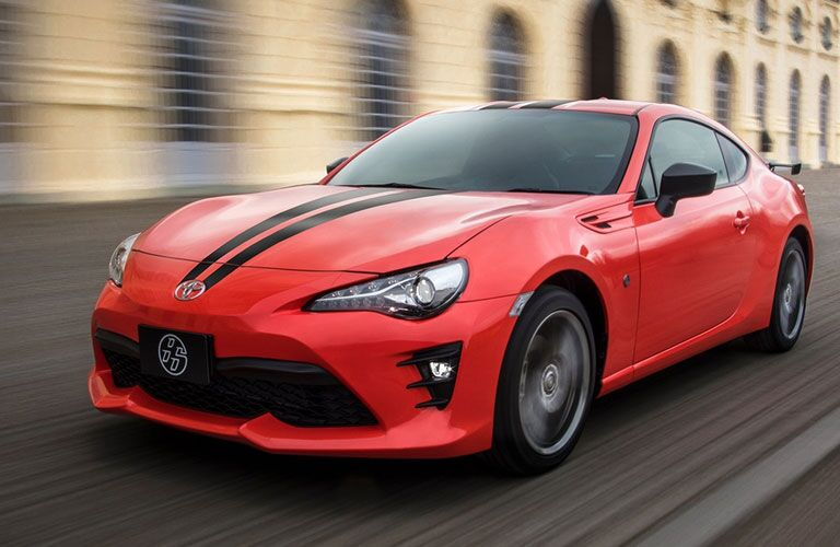 Exterior view of a red 2017 Toyota 86 driving down a city street