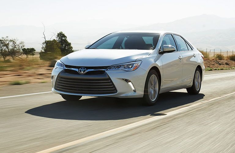 Exterior view of a silver 2017 Toyota Camry driving down a desert highway