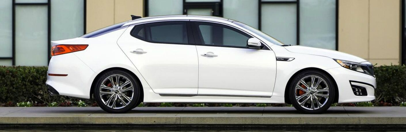 Exterior view of a white 2015 Kia Optima parked outside an office building