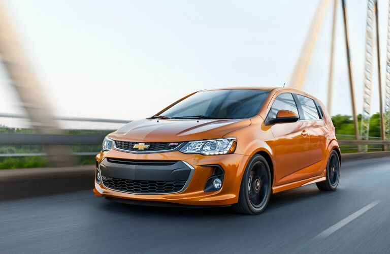 Exterior view of an orange 2017 Chevrolet Spark driving over a bridge