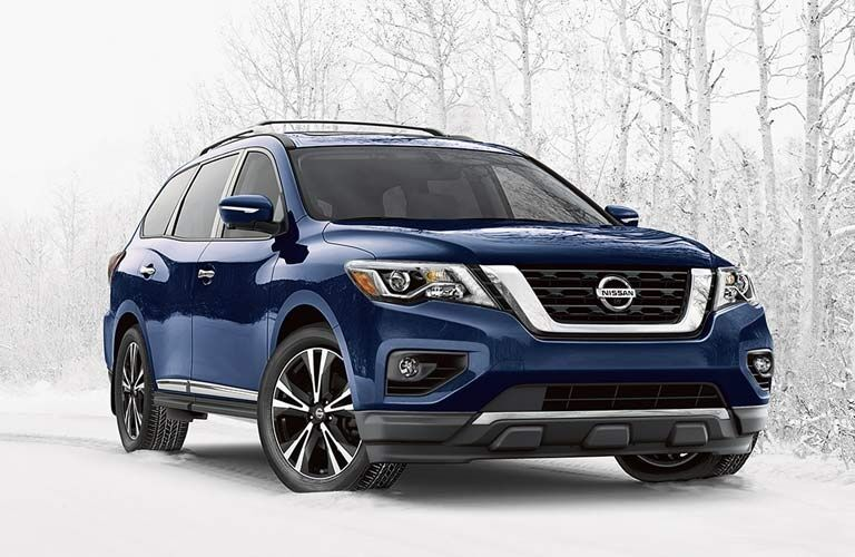 Exterior view of a blue 2017 Nissan Pathfinder parked in the snow