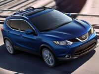 Exterior view of a blue 2017 Nissan Rogue Sport driving down the highway