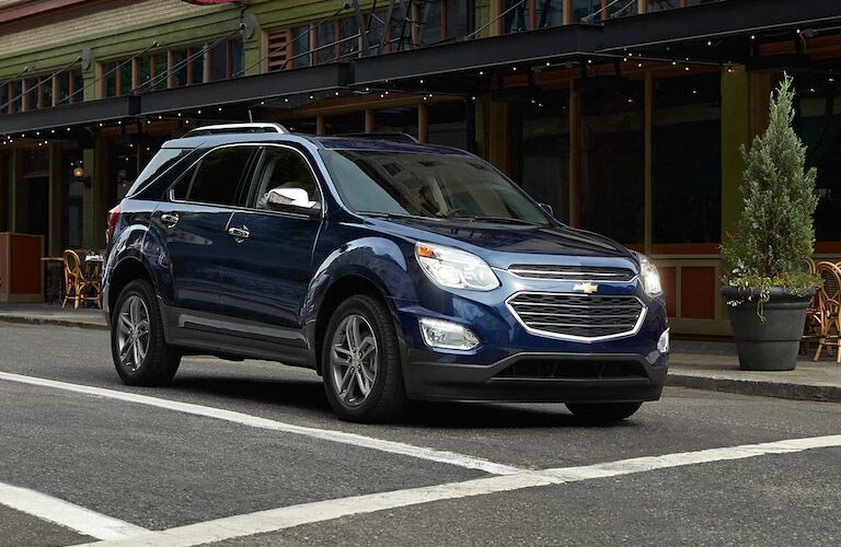 Exterior view of a blue 2017 Chevrolet Equinox stopped at an intersection in the city