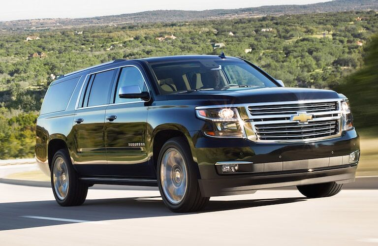 Exterior view of a black 2017 Chevrolet Suburban driving down a road