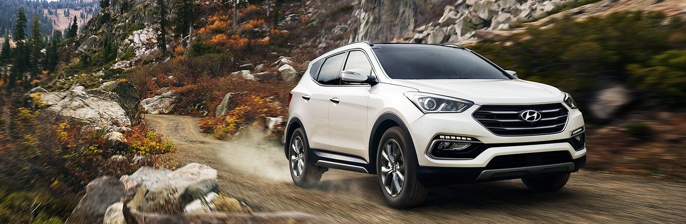 Exterior view of a white 2017 Hyundai Santa Fe Sport driving down a gravel road