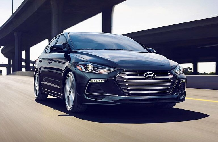 Exterior view of a black 2017 Hyundai Elantra driving down a highway exit ramp