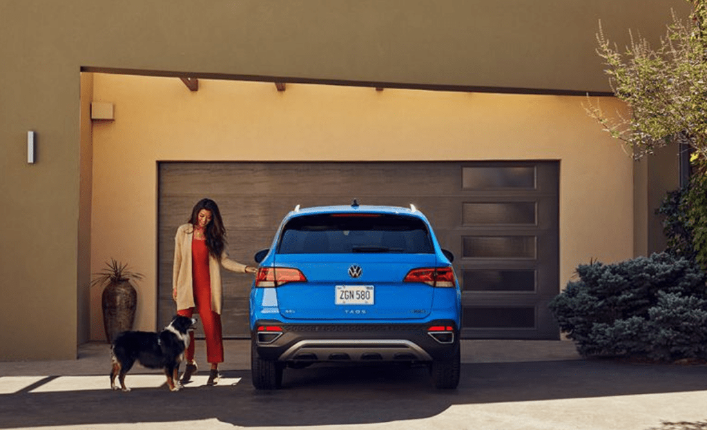 A woman with a dog going to a Volkswagen Taos parked in front of a garage.