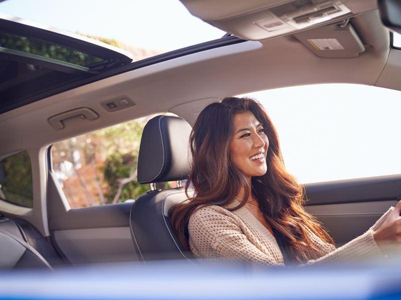 A smiling woman drives a VW Taos.