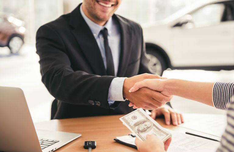 A photo of a person taking money from a dealership representative.