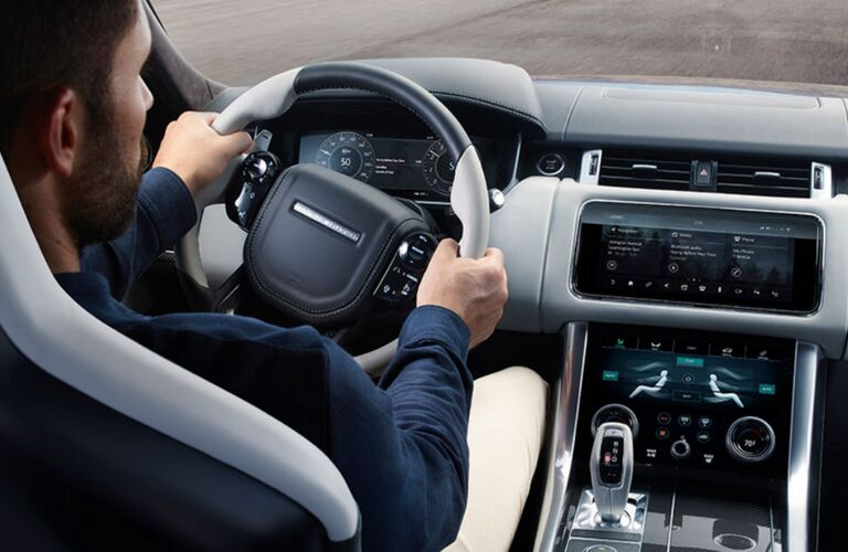 2018 Land Rover Range Rover Sport interior shot of driver with hands on steering wheel and dashboard infotainment running