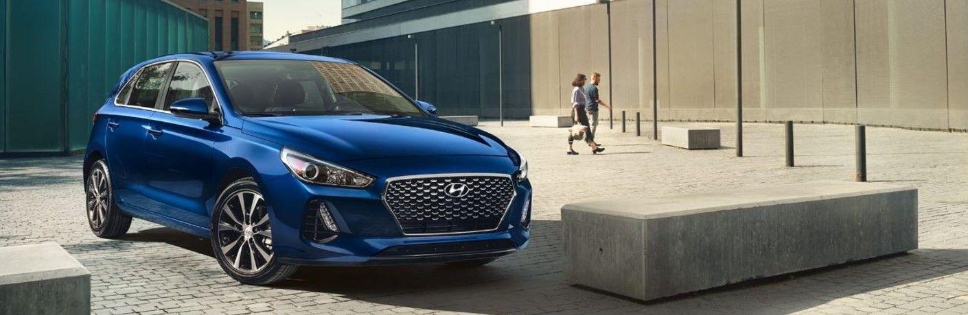 blue Hyundai Elantra GT parked by curb